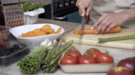 Unrecognisable woman chopping a carrot for her meal video
