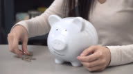 Unrecognisable woman putting coins in her piggy bank video