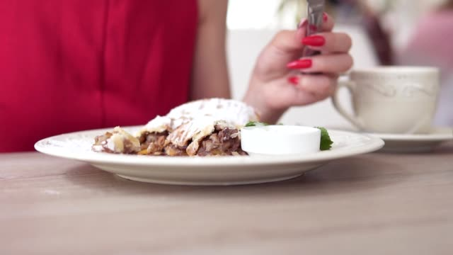 Unrecognizable girl in red dress eating dessert strudel at the restaurant using fork and knife. Beautiful white cup with coffee on the table. Slowmotion shot. video