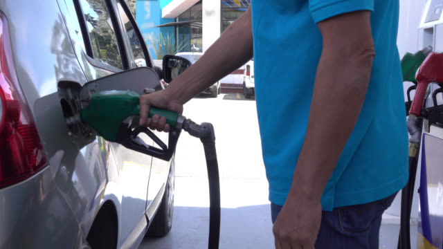 Unrecognizable man refueling his car at a gas station video