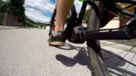 CLOSE UP: Unrecognizable man riding e-bike on empty road in modern suburban town video