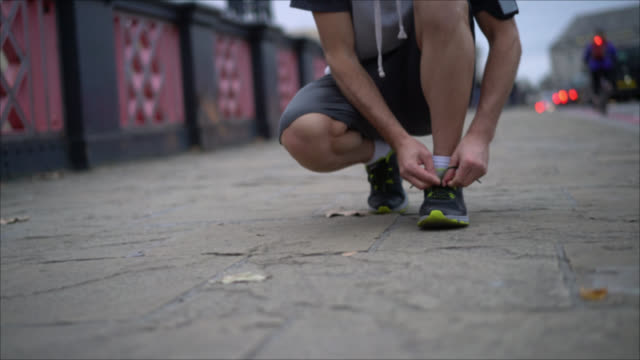 Unrecognizable man tying his tennis shoe  to start running video
