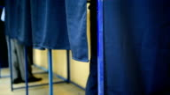 Unrecognizable people voting inside booths video