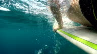 SLOW MOTION, UNDERWATER: Unrecognizable surfer paddling out catching reef break video