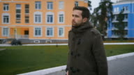 Unshaven man, tall walking along the path. He wore a gray coat. He is focused and serious. House of orange, blue and brown colors. In the yard Landscaped green lawn video