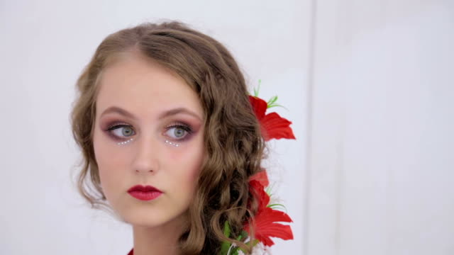 Unusual girl with creative make-up in dress looking at her reflection in mirror video