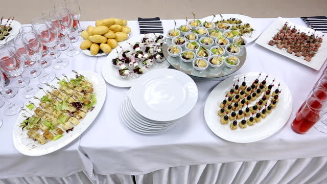 Up view of banquet table with appetizers, canapes, plates and glasses video