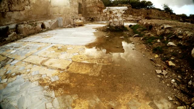 Upper part of antique column on ground puddle after rain Salamis Cyprus video
