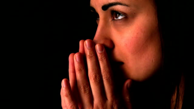 Upset brunette praying on black background video