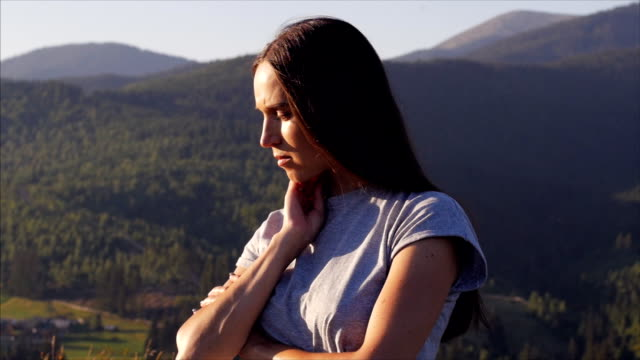 Upset female standing at sunset in mountains video