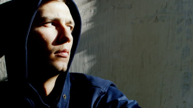 Upset young hooded man sitting near the window. The sun is shining spots on his face video