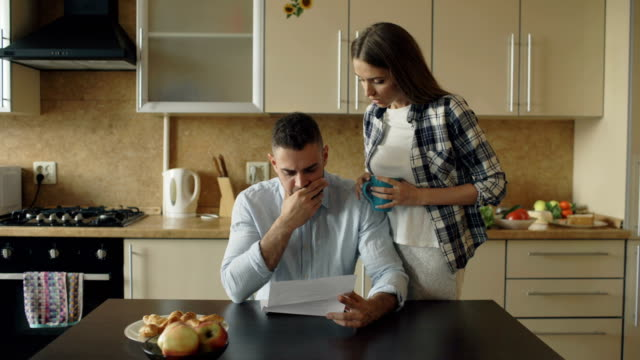 Upset young man reading unpaid bills and hugged by his wife supporting him in the kitchen at home video