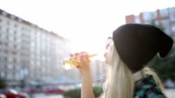 Urban blond girl drinking from a bottle video