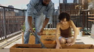 Urban Gardeners Putting Soil in Planter Box video