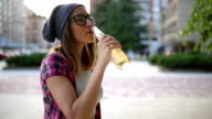 Urban girl drinking cider with friends video