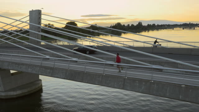 AERIAL Urban jogger on the bridge at sunset video