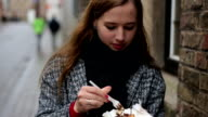 Urban portrait of young beautiful female tourist eating belgian waffle on street of Brugge, Belgium video