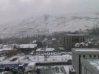 Urban Winter Scene; Snow Covered Buildings, Streets in front Mountains video