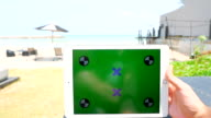 Using a digital tablet held by hands on the beach video