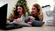 Using a laptop, girls communicate through the Internet, exchange e-mails, the winter season, the Christmas holidays in a cozy atmosphere near the fireplace video