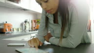 Using digital tablet and phone. Young woman, kitchen. video