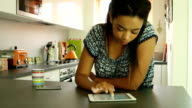 Using digital tablet. Young woman, kitchen. video
