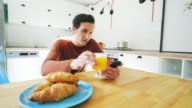 Using mobile phone while taking breakfast. video