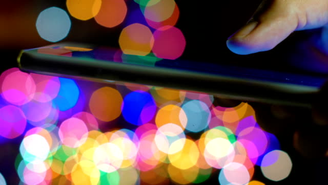 Using smartphone and christmas blurred lights on background video