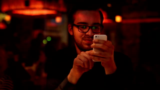 Using smartphone, cafe at night. video