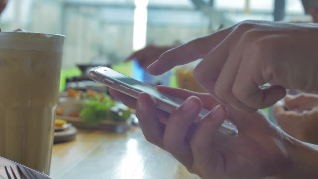 Using smartphone in restaurant,Close up video