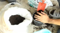 using trowel to put soil in a plastic pot video