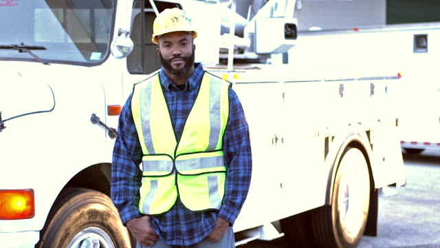 Utility worker in safety vest, by truck video