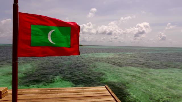 v00158 Maldives beautiful beach background white sandy tropical paradise island with blue sky sea water ocean 4k maldives maldivian flag video