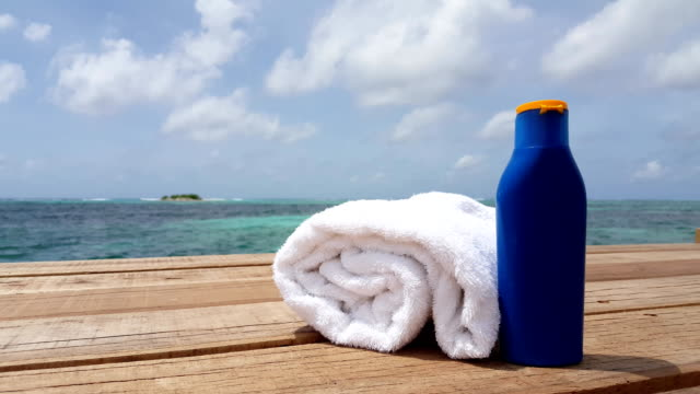 v00310 Maldives beautiful beach background white sandy tropical paradise island with blue sky sea water ocean 4k towel sun cream video