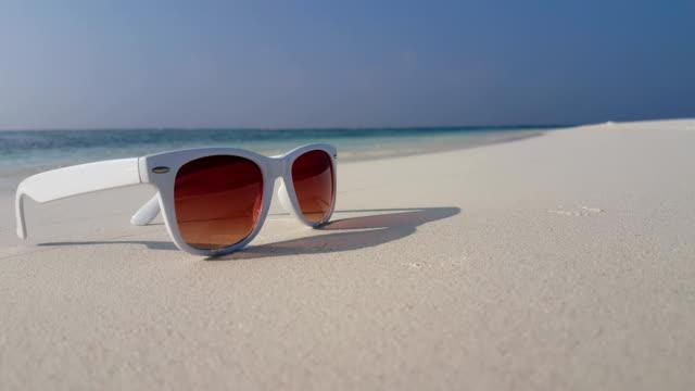 v01165 Maldives beautiful beach background white sandy tropical paradise island with blue sky sea water ocean 4k sunglasses video