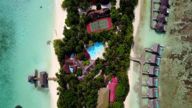 v03560 Aerial flying drone view of Maldives white sandy beach on sunny tropical paradise island with aqua blue sky sea water ocean 4k luxury 5 star resort hotel water bungalow hut relaxing holiday vacation video