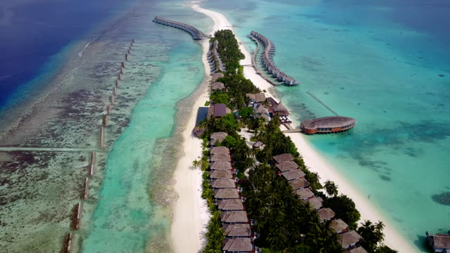 v03628 Aerial flying drone view of Maldives white sandy beach on sunny tropical paradise island with aqua blue sky sea water ocean 4k luxury 5 star resort hotel water bungalow hut relaxing holiday vacation video