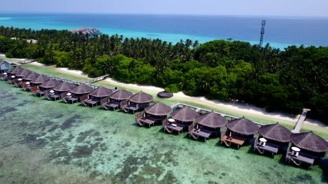 v03672 Aerial flying drone view of Maldives white sandy beach on sunny tropical paradise island with aqua blue sky sea water ocean 4k luxury 5 star resort hotel water bungalow hut relaxing holiday vacation video