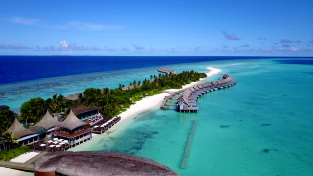 v03770 Aerial flying drone view of Maldives white sandy beach on sunny tropical paradise island with aqua blue sky sea water ocean 4k luxury 5 star resort hotel water bungalow hut relaxing holiday vacation video