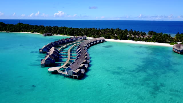 v03783 Aerial flying drone view of Maldives white sandy beach on sunny tropical paradise island with aqua blue sky sea water ocean 4k luxury 5 star resort hotel water bungalow hut relaxing holiday vacation video