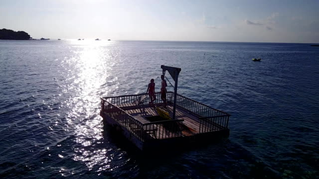 v03842 Aerial flying drone view of Maldives white sandy beach 2 people young couple man woman relaxing on sunny tropical paradise island with aqua blue sky sea water ocean 4k floating pontoon jetty sunbathing together video