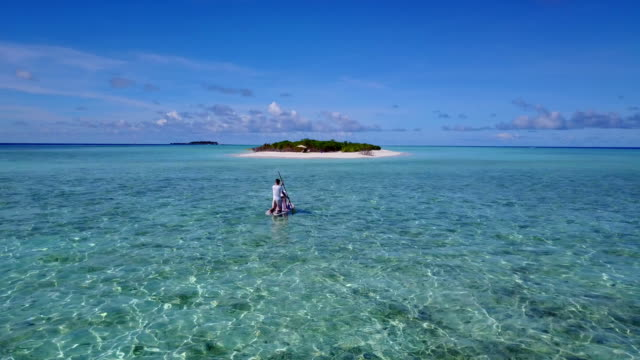 v03859 Aerial flying drone view of Maldives white sandy beach 2 people young couple man woman relaxing on paddleboard on sunny tropical paradise island with aqua blue sky sea water ocean 4k video