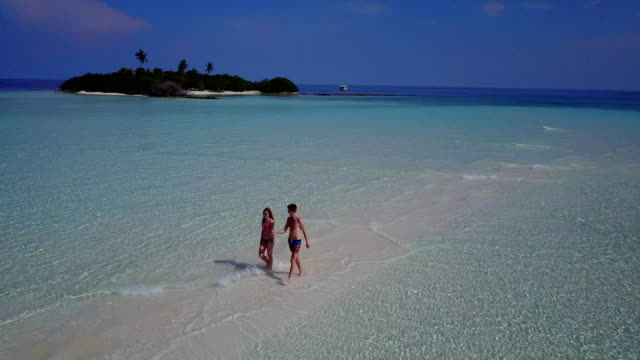 v03894 Aerial flying drone view of Maldives white sandy beach 2 people young couple man woman romantic love on sunny tropical paradise island with aqua blue sky sea water ocean 4k video