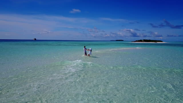 v03912 Aerial flying drone view of Maldives white sandy beach 2 people young couple man woman romantic love on sunny tropical paradise island with aqua blue sky sea water ocean 4k video
