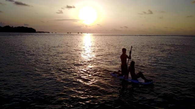 v04076 Aerial flying drone view of Maldives white sandy beach 2 people young couple man woman paddleboard rowing sunset sunrise on sunny tropical paradise island with aqua blue sky sea water ocean 4k video