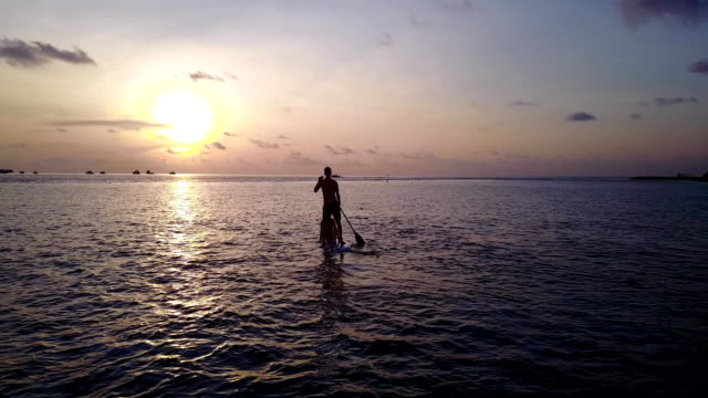 v04080 Aerial flying drone view of Maldives white sandy beach 2 people young couple man woman paddleboard rowing sunset sunrise on sunny tropical paradise island with aqua blue sky sea water ocean 4k video