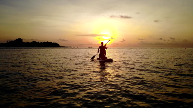 v04096 Aerial flying drone view of Maldives white sandy beach 2 people young couple man woman paddleboard rowing sunset sunrise on sunny tropical paradise island with aqua blue sky sea water ocean 4k video