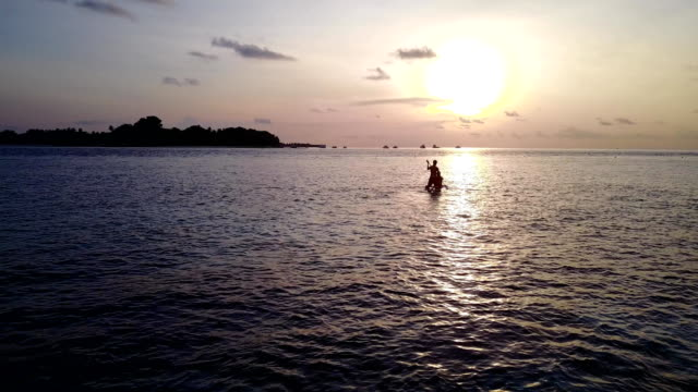 v04101 Aerial flying drone view of Maldives white sandy beach 2 people young couple man woman paddleboard rowing sunset sunrise on sunny tropical paradise island with aqua blue sky sea water ocean 4k video