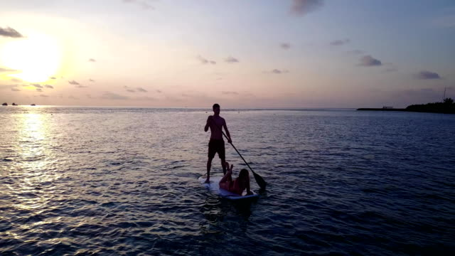 v04103 Aerial flying drone view of Maldives white sandy beach 2 people young couple man woman paddleboard rowing sunset sunrise on sunny tropical paradise island with aqua blue sky sea water ocean 4k video