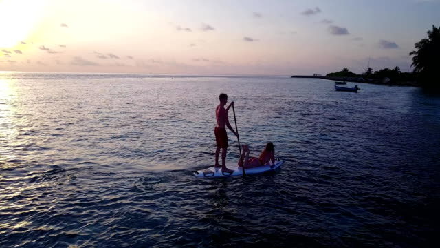 v04106 Aerial flying drone view of Maldives white sandy beach 2 people young couple man woman paddleboard rowing sunset sunrise on sunny tropical paradise island with aqua blue sky sea water ocean 4k video
